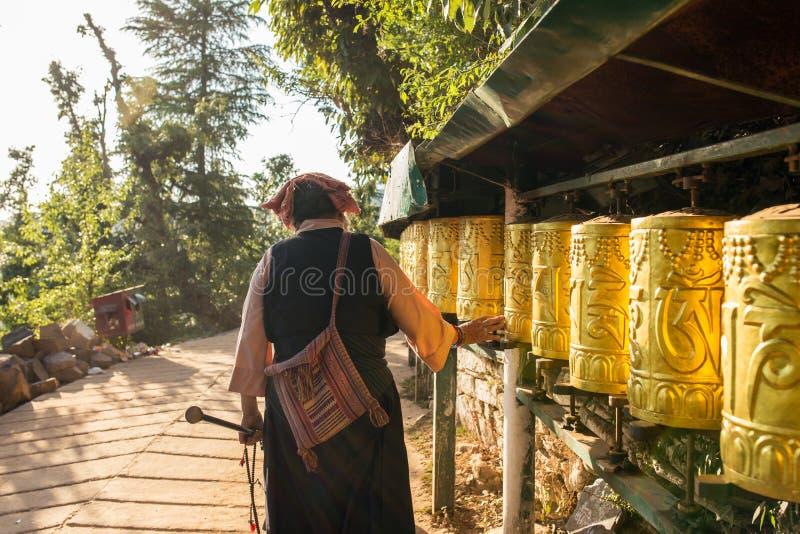 Unidentified tibetan woman spinning prayer wheels in Dharamsala, India stock photo