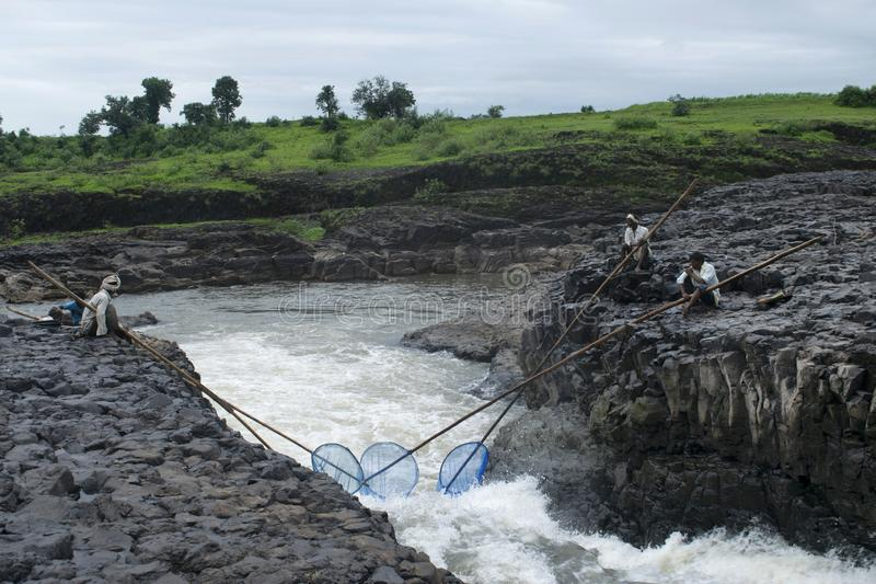 DHARNI, AMRAVATI, MAHARASHTRA, τον Αύγουστο του 2018, ψαράς που αλιεύει με τα δίχτυα στον καταρράκτη Utawali στο χωριό Utawali στοκ φωτογραφία με δικαίωμα ελεύθερης χρήσης