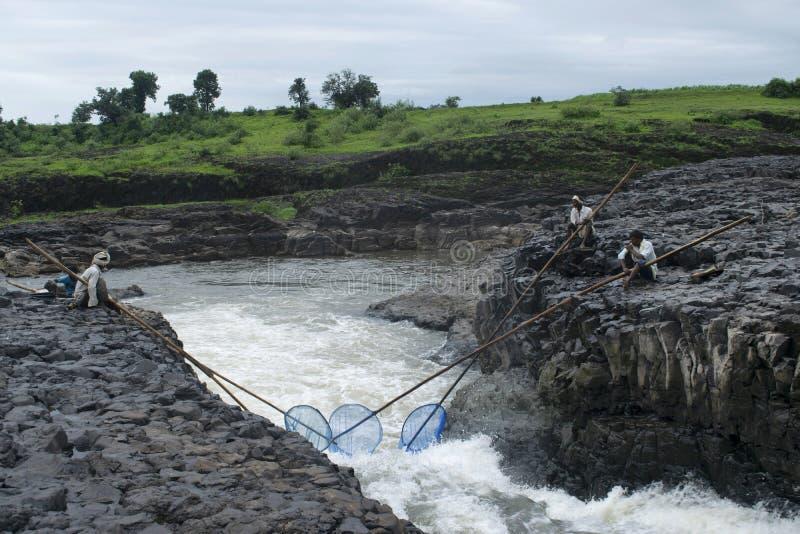 DHARNI, AMRAVATI, MAHARASHTRA, agosto de 2018, pesca del pescador con las redes en la cascada de Utawali en el pueblo de Utawali fotografía de archivo libre de regalías