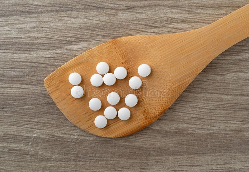 DHEA pills on a wood spoon atop a table top view royalty free stock photo