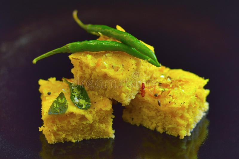 Dhokla Indian dish with chili on a black background royalty free stock photo