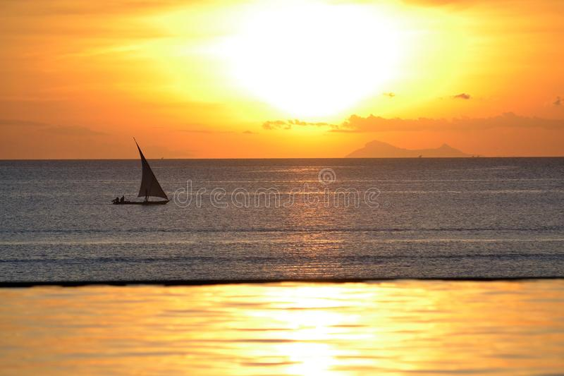 Dhow Boat at sunset. Dhow Boat sailing by during a sunset in Zanzibar from infinity pool stock photo