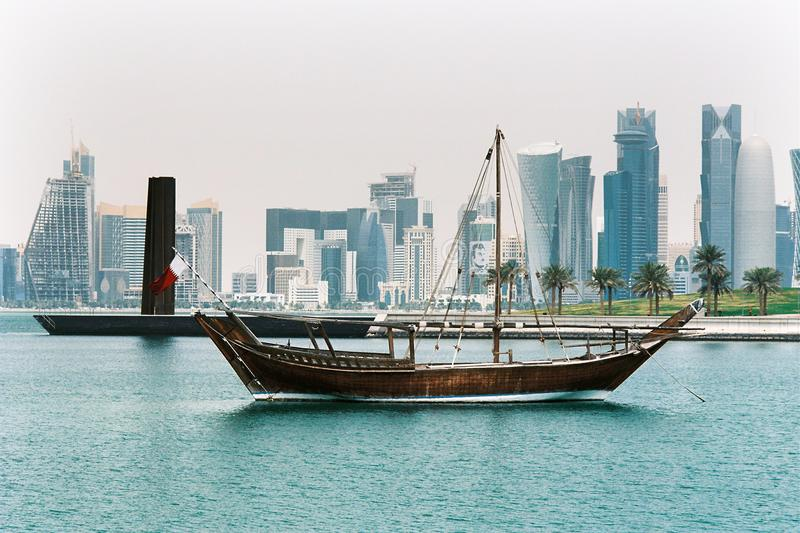 Dhow in doha with towers royalty free stock image
