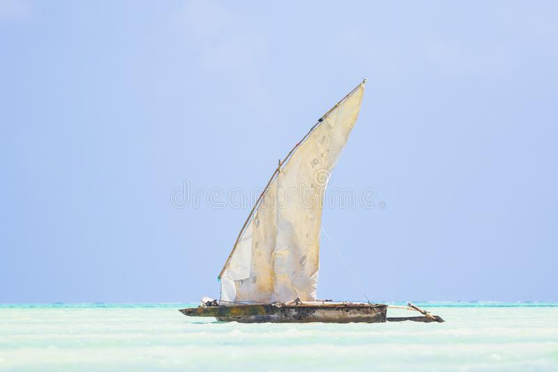 Dhow wooden boat with sail in a tropical clear blue sea at the Indian Ocean royalty free stock photography