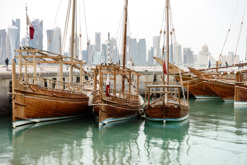 Dhows arbour Doha Qatar. Traditional dhows with flags of Qatar are docked in harbor of Doha, such vessels are popular for tourist trips along the coast, Qatar stock photography