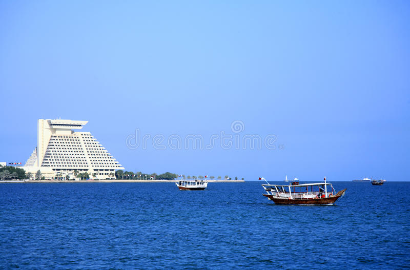 Dhows in Doha Bay, Qatar. Three dhows ferrying sightseers ply the waters of Doha Bay, Qatar, Arabia, while the bulk of a landmark hotel looms behind them stock photography