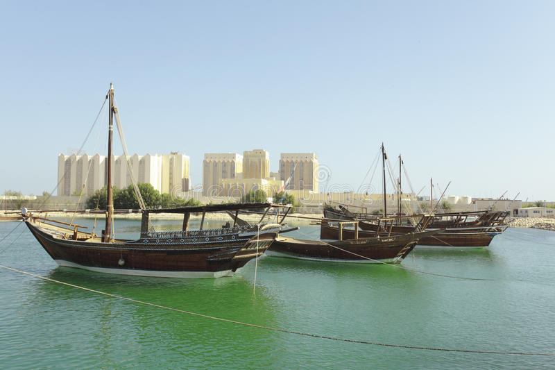 Dhows and Doha Port buildings,. Dhows moored off Museum Park in central Doha, Qatar, Arabia, with some of the buildings from the city's commercial port in the stock photos