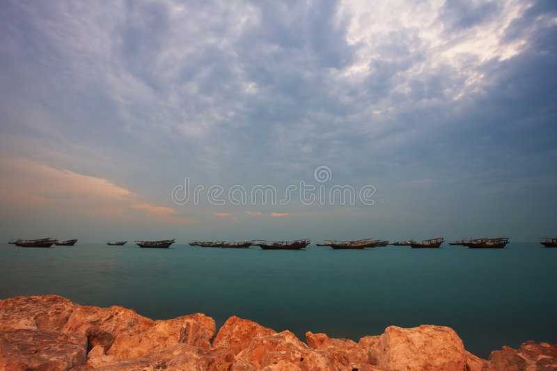 Dhows at sunrise. Fishing dhows at the harbour of the old pearling town of Al Wakrah in Qatar, Middle East, right before sunrise (movement on the Dhows stock image