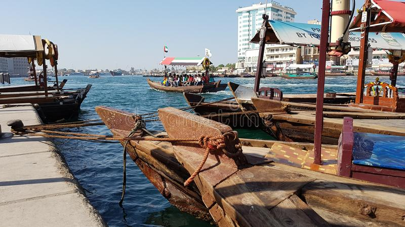 Dhows tied up in Dubai Creek. Dhows tied up in a harbor, Dubai Creek, with modern buildings in the background stock photo