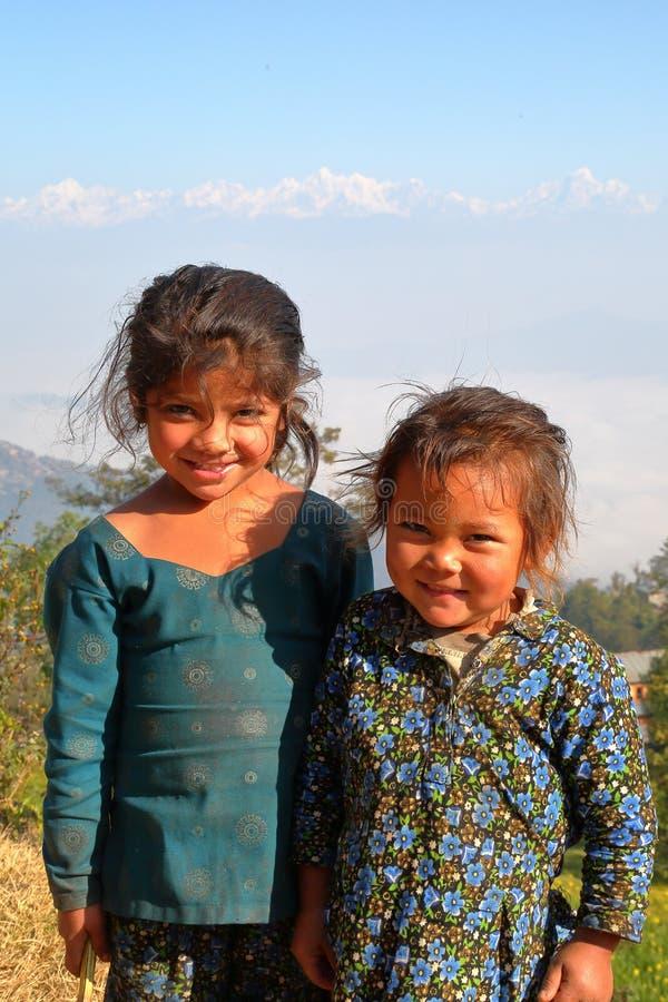 DHULIKHEL, NEPAL - 25 DE DEZEMBRO DE 2014: Retrato de duas meninas bonitos com as montanhas Himalaias no fundo fotografia de stock royalty free