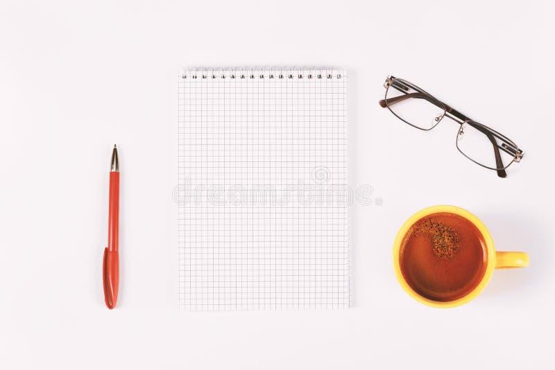 Diário, pena, xícara de café e vidros vazios na tabela branca imagem de stock royalty free