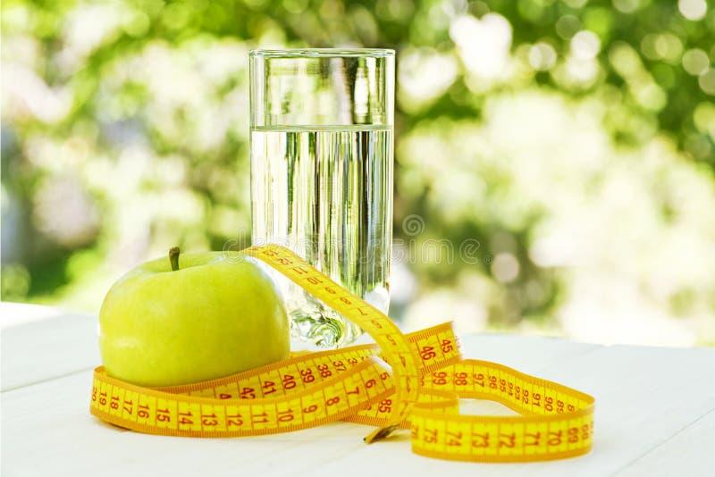 Diät Ein Apfel mit Wasser und messendem Band auf einem weißen Holztisch auf grünem natürlichem Hintergrund Stellen Sie schützende stockfoto