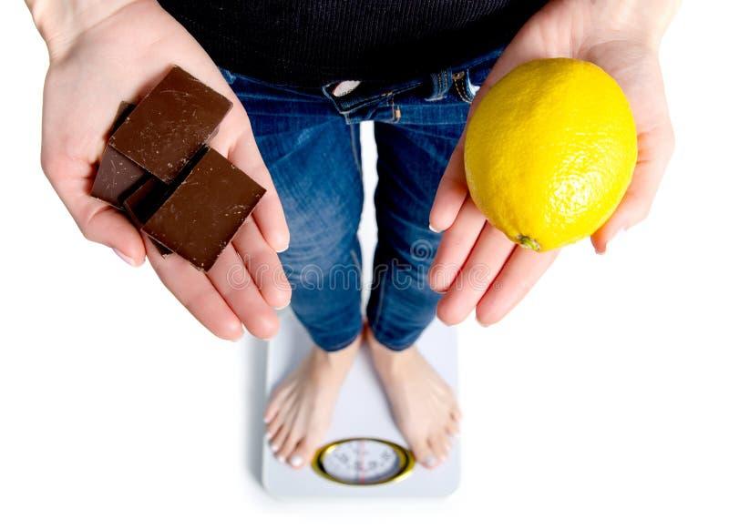Diät Frauen-messendes Körpergewicht auf der wiegenden Skala, die Schokolade und Zitrone hält lizenzfreie stockbilder