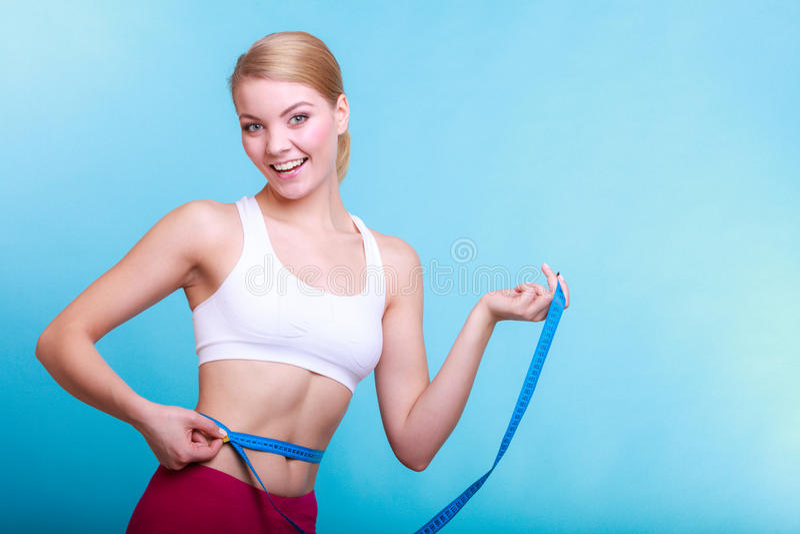 Diät. Geeignetes Mädchen der Eignungsfrau mit dem Maßbandmessen ihre Taille stockbild