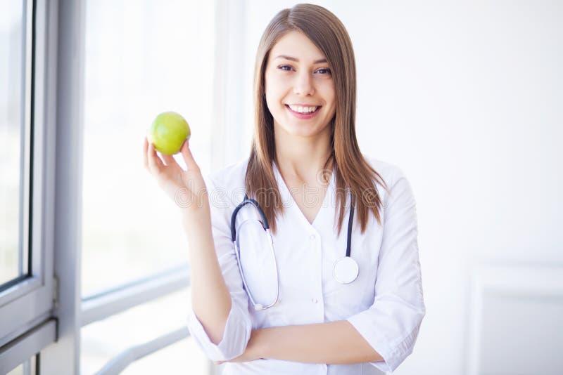 Diät Glückliche Arztfrau, die Apfel und Stethoskop zeigt stockfoto