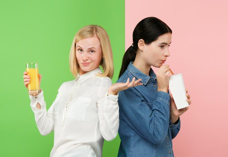 Diät Nährendes Konzept Gesunde Nahrung Schöne junge Frauen, die zwischen Orangensaft der Frucht und unhelathy karbonisiert wählen lizenzfreie stockbilder