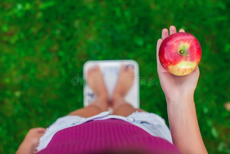 Diät- und Gewichtskonzept Junge Frau, die auf einer Skala mit steht lizenzfreie stockfotos