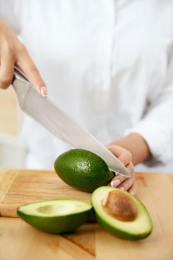 Diät Weibliche Hände, die Avocado in der Küche schneiden stockfotos