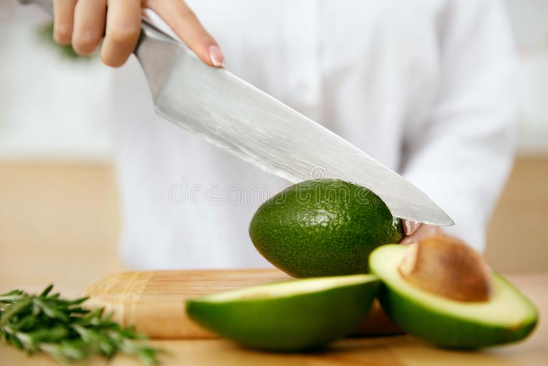Diät Weibliche Hände, die Avocado in der Küche schneiden lizenzfreie stockbilder