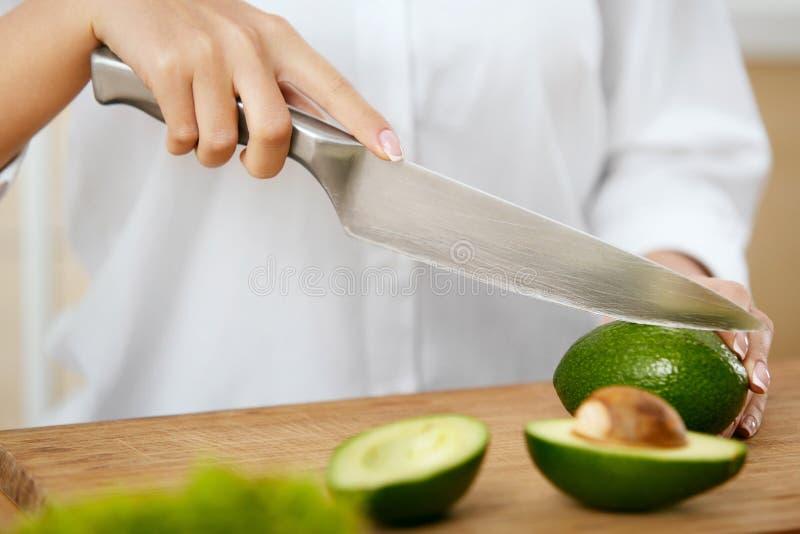 Diät Weibliche Hände, die Avocado in der Küche schneiden lizenzfreies stockbild