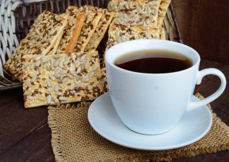Diätetischer knuspriger Cracker mit Getreide (Sonnenblumensamen, Flachs und indischer Sesam) und einer Tasse Tee stockbilder