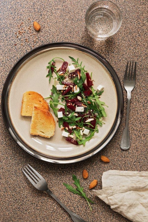 Diätetischer Salat des frischen strengen Vegetariers mit Rote-Bete-Wurzeln, Arugula, Feta, Nüssen und Samen über braunem Steinhin lizenzfreies stockfoto