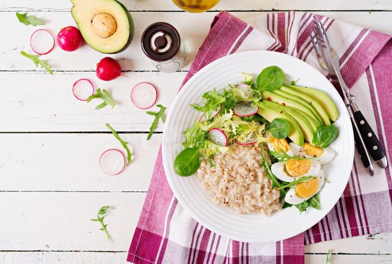 Diätetisches Menü des gesunden Frühstücks Hafermehlbrei und Avocadosalat und -eier stockbild