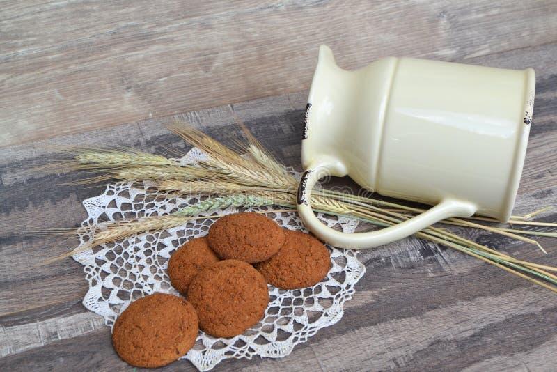Diäthafermehlplätzchen auf einer gestrickten Serviette und einem Krug, schäbiger Hintergrund lizenzfreies stockfoto