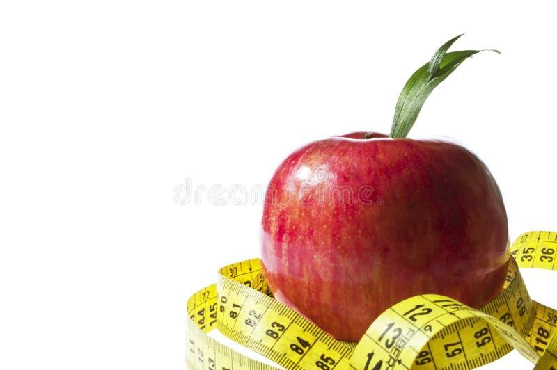 Diätkonzept - rotes Apfel- und Maßband stockfotografie
