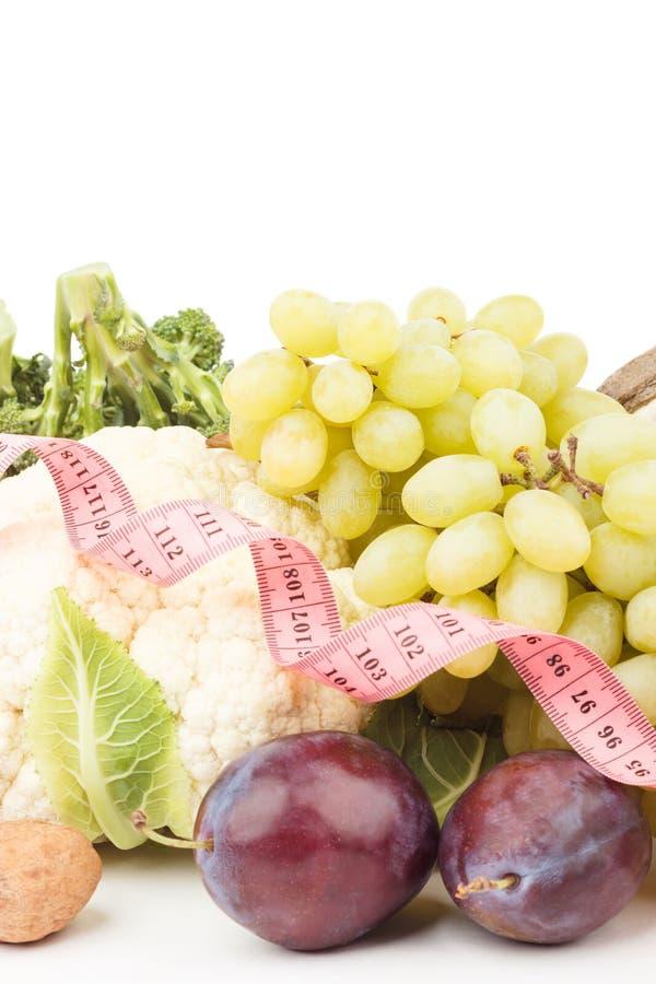 Diätkonzept: Stellen Sie vom Blumenkohl, von der grünen Traube, von der Walnuss und von der Pflaume mit messendem Band ein lizenzfreies stockbild