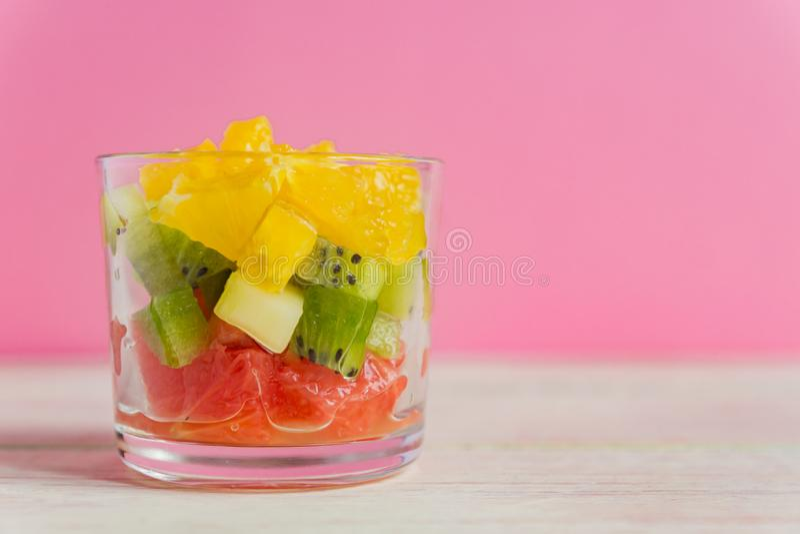 Diète Une salade de fruits fraîche et savoureuse dans un pot de verre sur fond rose. Oranges juteuses hachées, kiwi et pamplemo image stock
