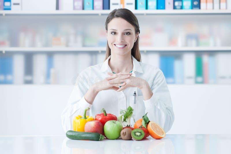 Diététicien de sourire avec les légumes sains images libres de droits