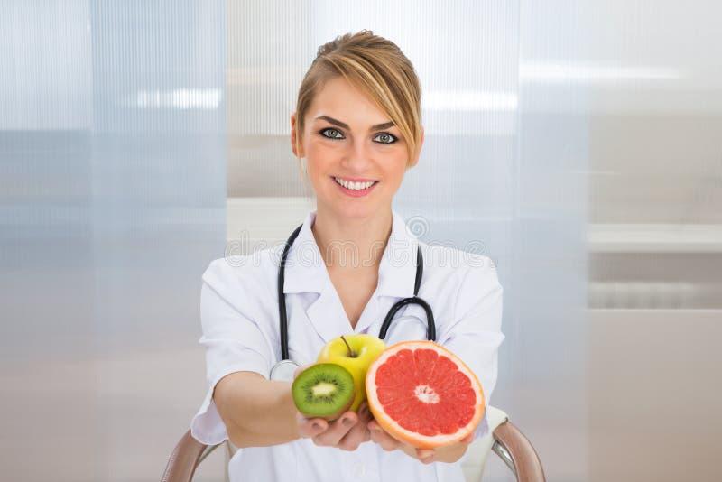 Diététicien féminin tenant des fruits photo stock