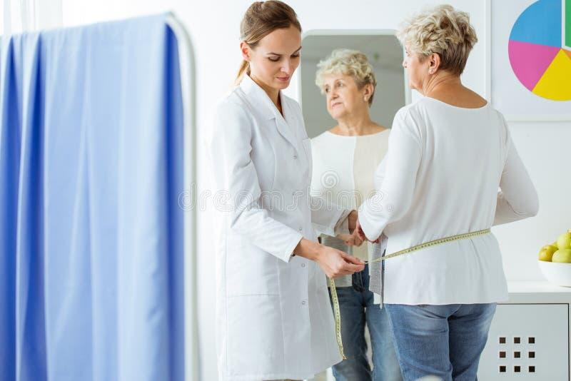 Diététicien mesurant le circuit patient de corps du ` s images libres de droits