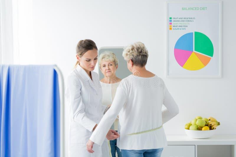 Diététicien mesurant le circuit patient de corps du ` s image stock