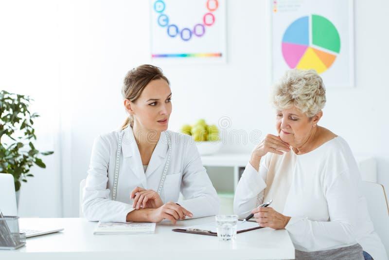 Diëtist en patiënt met problemen stock afbeelding