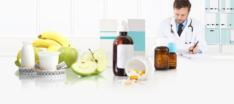 Diëtistenvoedingsdeskundige de arts schrijft voorschriftzitting op het bureaukantoor met voor appel, yoghurt, medische drugs en b royalty-vrije stock foto