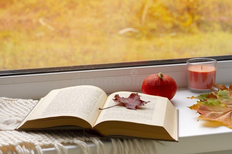 Di autunno vita ancora libri, foglie, tazza e candeliere sulla finestra immagini stock libere da diritti