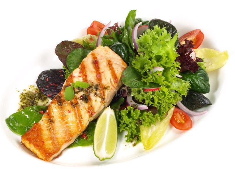Di color salmone arrostito - filetto di pesce con insalata immagine stock
