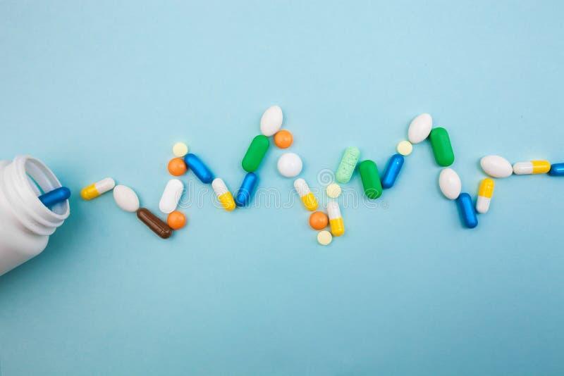 di compresse e di capsule colorate Multi in bottiglia bianca di battito cardiaco di pulsazione per le compresse, pillole farmaceu fotografie stock