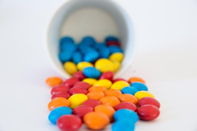 di confetti rotondi colorati Multi delle caramelle rovesciati da una tazza di carta invertita immagine stock
