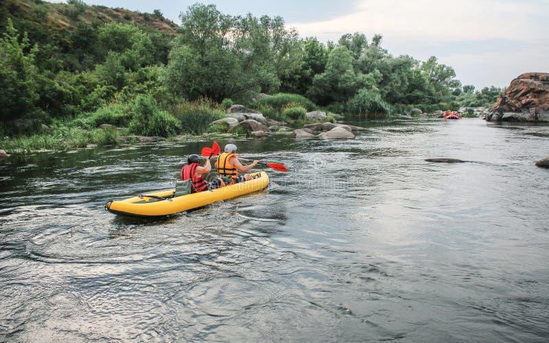 Di due uomini goda dell'attività di rafting dell'acqua al fiume Famiglia di rafting in vacanza fotografia stock libera da diritti
