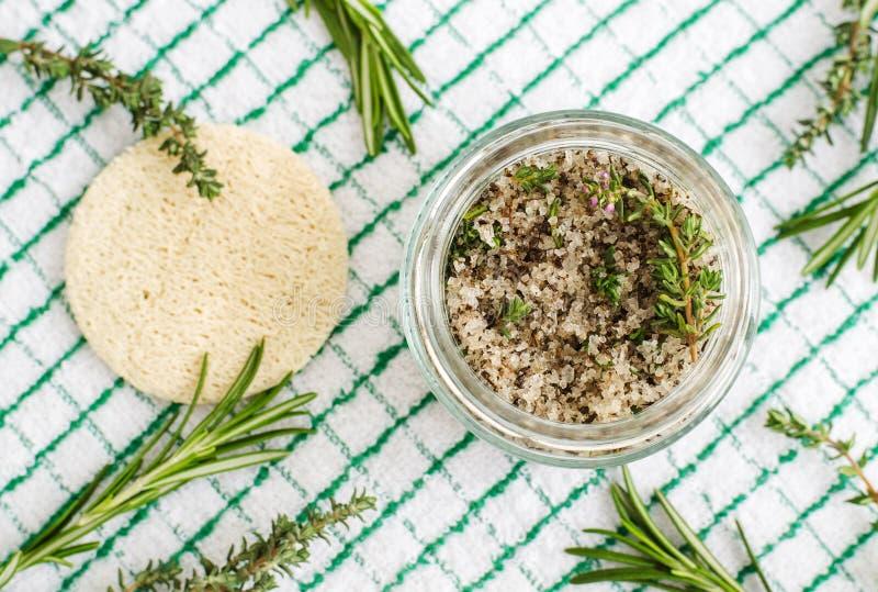 Di erbe casalinghi sfregano il piede per inzupparsi o il sale da bagno con i rosmarini, il timo, il sale marino e l'olio d'oliva  immagine stock