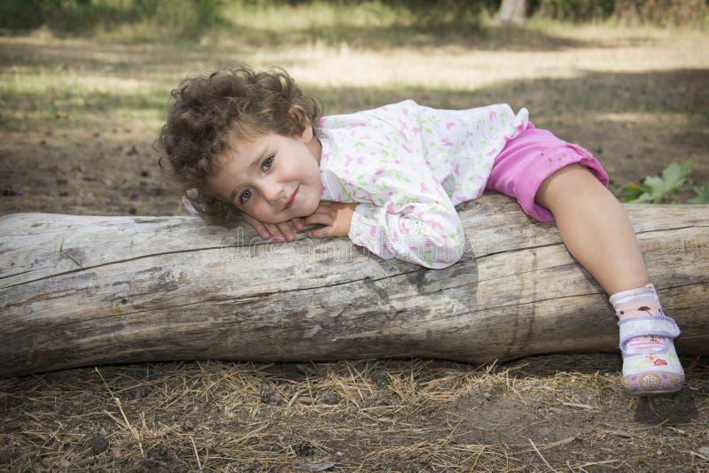 di estate nel legno sul ceppo si trova una piccola ragazza riccia S fotografie stock libere da diritti