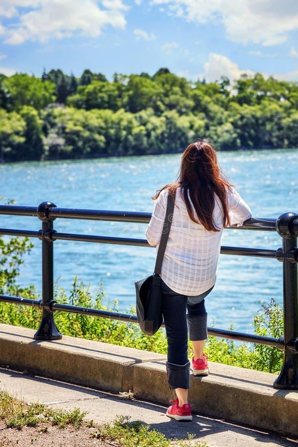Di fronte alla giovane donna caucasica posteriore della testarossa guarda il fiume su un ponte un giorno di estate soleggiato immagini stock
