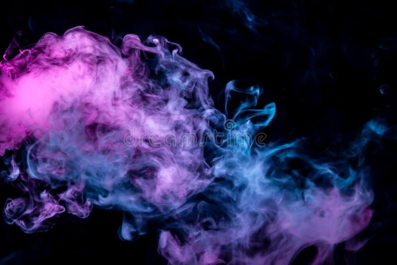 Di fumo ondulato porpora e blu rosa su un fondo isolato nero Modello astratto di vapore da vape delle nuvole aumentanti fotografie stock