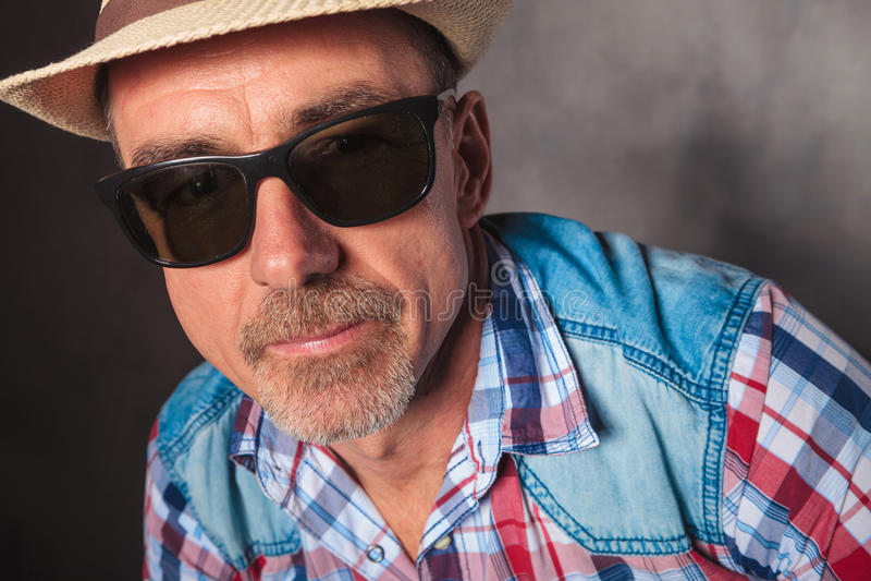 Di gran lunga del cappello d'uso e degli occhiali da sole dell'uomo maturo fotografie stock
