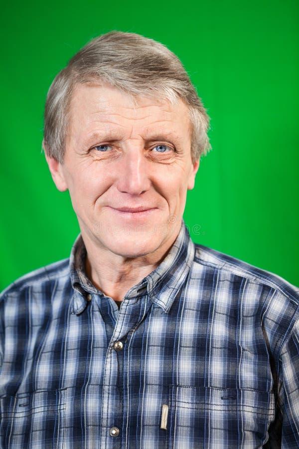 Di gran lunga ritratto dell'uomo sorridente maturo, fondo verde fotografia stock