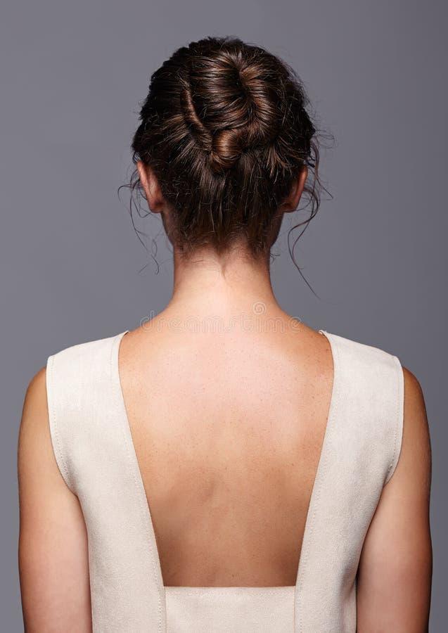 Di gran lunga di una giovane donna dal lato posteriore H femminile immagini stock
