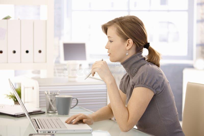 Di impiegato attraente che si siede allo scrittorio fotografia stock